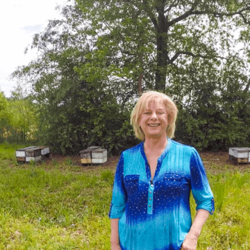 A photo of Beekeeper Jane Collins standing in front of beehives in her bee yard.