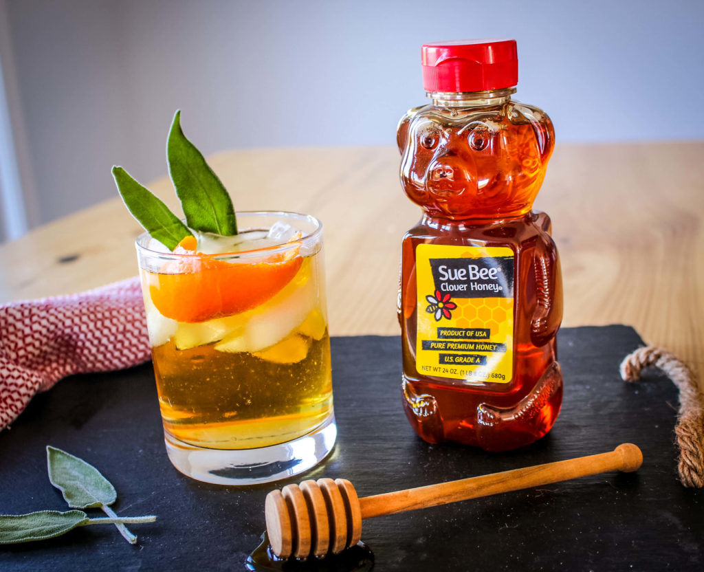 Photo of Sue Bee® honey and a drink with sage leaves.
